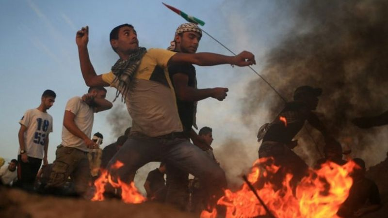 পাথর ছুঁড়ে ফিলিস্তিনি তরুণরা লড়ছে ইসরায়েলি সৈন্যদের বিরুদ্ধে
